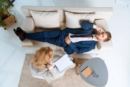 Photo for Overhead view of psychologist working with young businessman lying on couch - Royalty Free Image