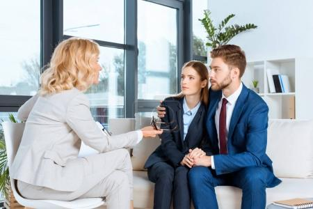 Photo for Young couple embracing and looking at psychologist in office - Royalty Free Image
