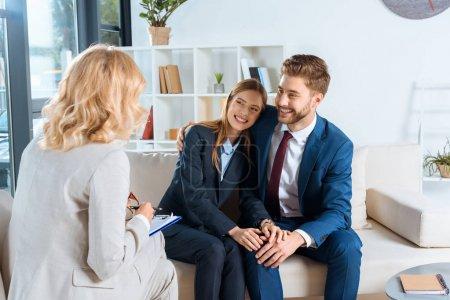 Photo pour Sourire jeune couple regardant psychothérapeute au bureau - image libre de droit