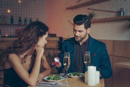 Photo pour Homme faisant la demande en mariage à petite amie lors d'un dîner romantique au restaurant - image libre de droit