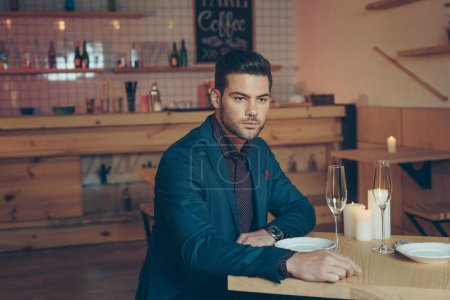 Photo for Portrait of stylish pensive man sitting at table in restaurant - Royalty Free Image