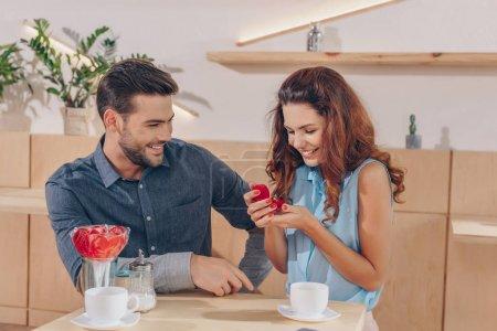 Photo pour Portrait de femme heureuse regardant bague de fiançailles dans les mains en cae - image libre de droit
