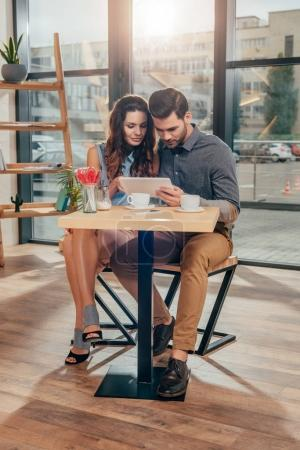 couple using tablet in cafe