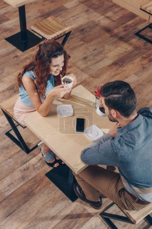 Photo for High angle view of couple drinking coffee while spending time together in cafe - Royalty Free Image