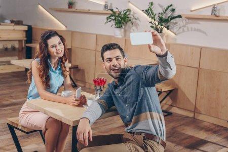 Photo pour Prise de couple gai selfie sur smartphone dans café - image libre de droit