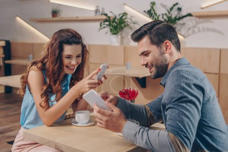 couple with smartphones in cafe
