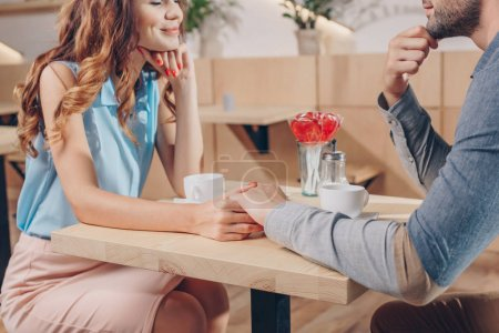 Photo for Cropped shot of couple holding hands while having date in coffee shop - Royalty Free Image