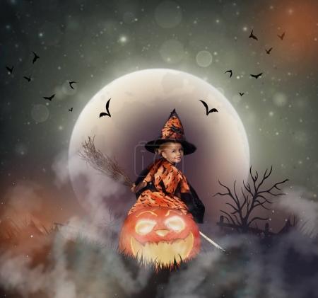 Photo pour Enfant souriant en costume d'Halloween de sorcière avec balai assis sur grand Jack o lanterne à la nuit d'Halloween avec lune et brume - image libre de droit