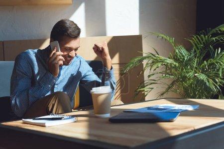 Photo pour Jeune homme d'affaires gai parler sur smartphone tout en buvant du café au café - image libre de droit