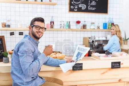 Photo pour Beau jeune homme souriant dans les lunettes de lecture de journaux et de boire du café dans le café - image libre de droit