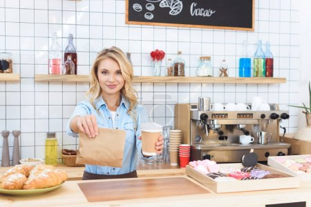 Photo pour Belle jeune serveuse tenant du café pour aller emporter de la nourriture dans le café - image libre de droit