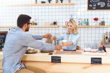 Photo pour Belle jeune serveuse donnant tasse en papier et emporter de la nourriture au client dans le café - image libre de droit