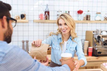 Photo pour Jeune serveuse souriante donnant du café pour aller et sac en papier avec de la nourriture au client dans le café - image libre de droit