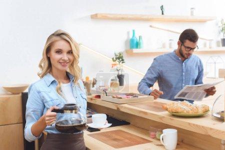 Photo pour Belle jeune serveuse souriante tenant cafetière et tasse tandis que le client lisant le journal derrière - image libre de droit