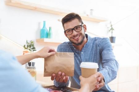 Photo pour Serveuse donnant du café pour aller et sac en papier avec de la nourriture à emporter à sourire jeune client dans le café - image libre de droit