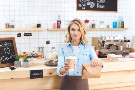 Photo pour Jeune serveuse souriante tenant du café pour aller dans une tasse en papier et emporter de la nourriture dans un sac en papier - image libre de droit