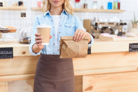 Photo for Cropped shot of waitress holding coffee to go in paper cup and take away food in paper bag - Royalty Free Image