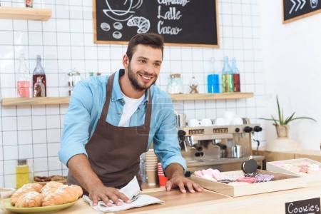 Photo pour Beau sourire jeune barista nettoyage bar comptoir et détourner les yeux - image libre de droit