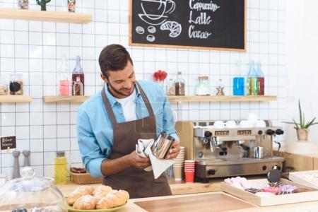 Photo pour Beau sourire jeune barista séchage ustensile avec serviette - image libre de droit