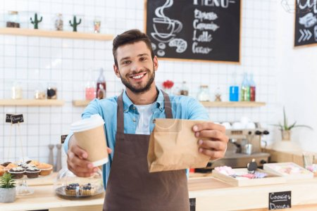 Photo for Handsome smiling young barista holding coffee to go in paper cup and take away food in paper bag - Royalty Free Image