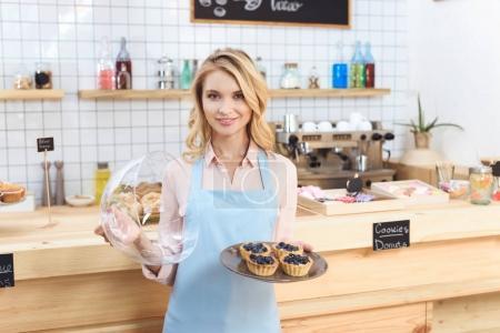 Photo pour Belle jeune serveuse tenant des gâteaux et souriant à la caméra dans le café - image libre de droit
