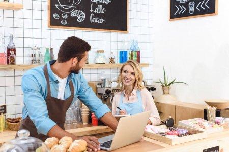 Foto de Feliz pareja joven de los dueños de café usando laptop y sonriendo unos a otros - Imagen libre de derechos