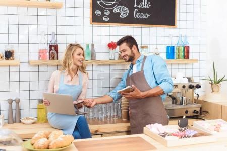 Photo pour Souriant jeune propriétaire de café tenant ordinateur portable et ordinateur portable tout en travaillant ensemble - image libre de droit