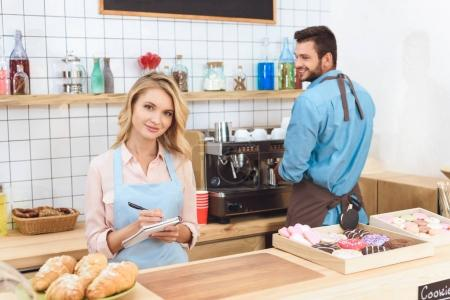 Photo for Beautiful young waitress taking notes and smiling at camera while barista making coffee behind - Royalty Free Image