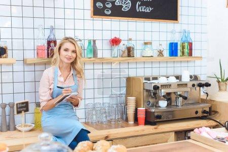 Photo pour Attrayant jeune propriétaire de café prenant des notes et souriant à la caméra - image libre de droit