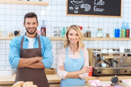Photo for Confident young cafe workers standing with crossed arms and smiling at camera - Royalty Free Image