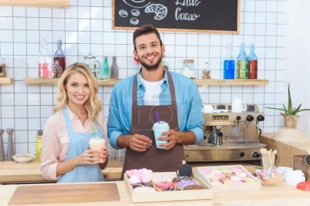 Photo pour Joyeuse jeune barista et serveuse tenant milkshakes et souriant à la caméra - image libre de droit