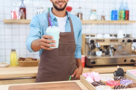 Photo pour Plan recadré de barista souriant tenant latte dans une tasse en plastique - image libre de droit