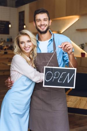 Photo pour Joyeux jeunes propriétaires de café tenant signe ouvert et souriant à la caméra - image libre de droit