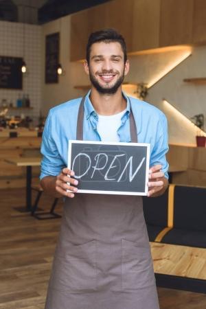 Photo pour Beau jeune propriétaire de petite entreprise tenant signe ouvert et souriant à la caméra - image libre de droit