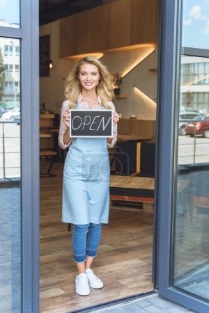 Photo pour Attrayant jeune serveuse tenant signe ouvert et souriant à la caméra - image libre de droit