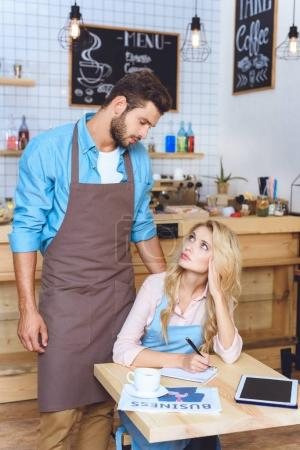 Photo pour De jeunes propriétaires de café sérieux qui se regardent tout en travaillant ensemble - image libre de droit