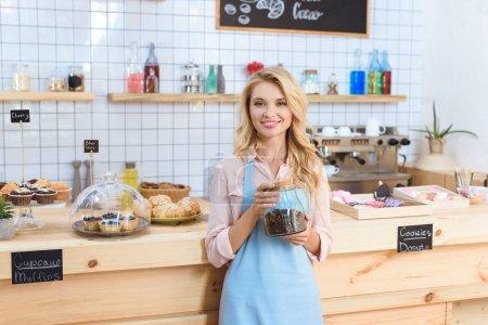 Photo pour Attrayant jeune serveuse tenant grains de café dans un bocal en verre et souriant à la caméra dans le café - image libre de droit