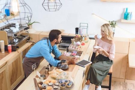Photo pour Vue grand angle de jeune barista regardant belle femme buvant du café dans le café - image libre de droit