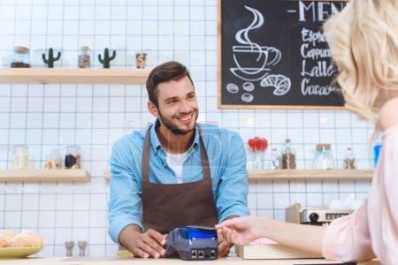 Photo pour Plan recadré de la femme tenant la carte de crédit tout beau serveur souriant en utilisant le terminal de paiement - image libre de droit