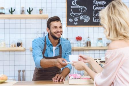 barista giving coffee to client