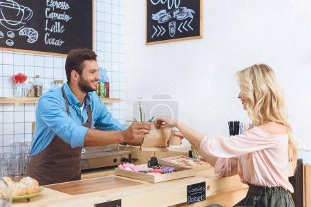 Photo pour Beau jeune garçon donnant emporter de la nourriture et du café dans une tasse en papier à une femme souriante dans un café - image libre de droit
