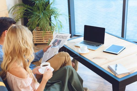 couple with newspaper and coffee