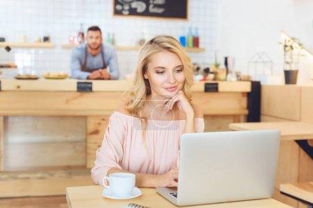 Photo pour Belle jeune femme souriante en utilisant un ordinateur portable dans le café - image libre de droit