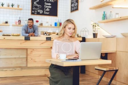 woman using laptop in cafe