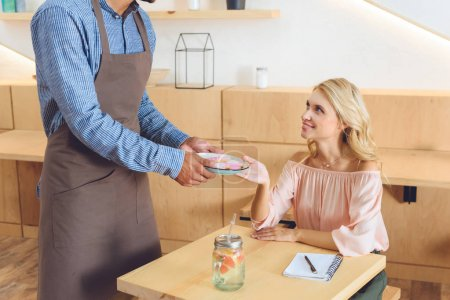 Photo pour Plan recadré de serveur dans tablier donnant des cookies au client souriant - image libre de droit