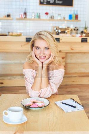 Photo pour Belle jeune femme souriant à la caméra tout en étant assis à table avec les cookies et portable au café - image libre de droit