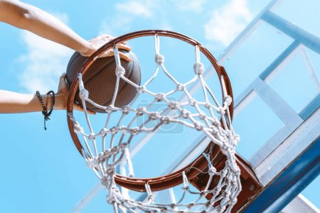 Hands throwing ball into basket