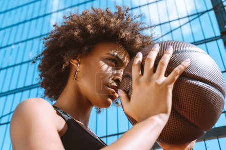 Photo for Young african-american woman in sports bra holding basketball ball, adjusting her aim - Royalty Free Image