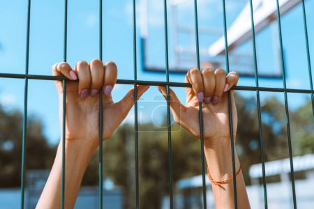 Hands clinging onto fencing