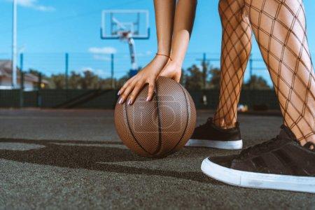 woman placing basketball on ground